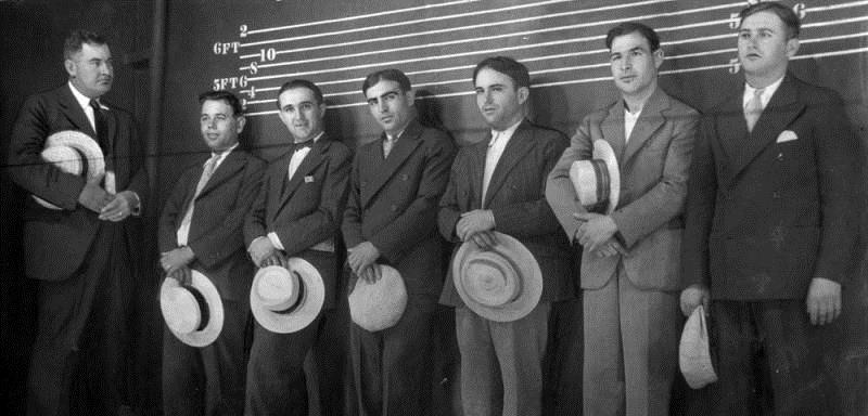 "Photo shows six asserted racketeers lined up in the Los Angeles police shadowbox today while detectives look them over in effort to link them with six gang murders. The men stand behind a thin screen in a stage-like box. It is illuminated so the suspects can be clearly seen by detectives, but cannot see the detectives inspecting them from the darkness. Left to right, Detective Lieutenant 'Lefty' James, John Testini, Dominic de Soto (aka Domenico Di Ciolla), alleged rival of slain August Palombo; Vito Cisareo, Domenic Shiovone, Salvadore Verna, Louis Tasselli."" Los Angeles Herald Examiner, July 26, 1928."
