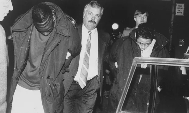 Yusef Salaam, left, is led away by a detective after being arrested in Central Park.